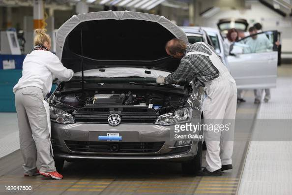 Volkswagen employees do a final check on a new VW Golf VII car at the Volkswagen factory on February 25 2013 in Wolfsburg Germany Volkswagen will...