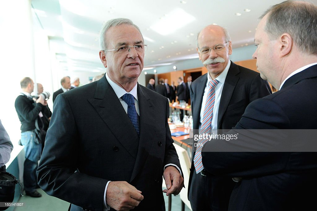 Volkswagen group's CEO Martin Winterkorn, Daimler CEO Dieter Zetsche and the chairman of Germany's second biggest-power supplier RWE, Peter Terium, stand together prior to a meeting on October 1, 2012 in Berlin. Merkel had invited leading representatives of science and economy for talks on electromobility.
