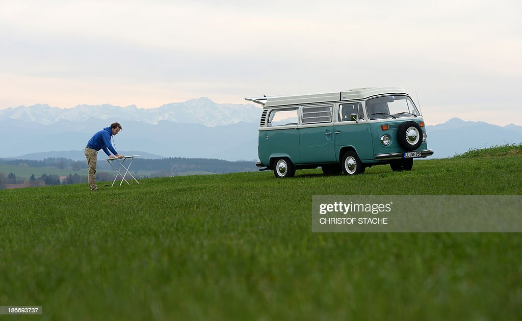 Volkswagen Kombi owner Wanja Fuhrmann sets up a camping table next to his Volkswagen T2 camper van built in the year 1975 near Landsberg, southern Germany, on November 1, 2013. VW's kombi, camper van or Bulli as it is nicknamed in Germany has meant road trips for generations of families, and from surfers to hippies, in search of that perfect wave or trip, the van represented freedom. But times have changed and in Brazil, the last country in the world still producing the vehicles, new auto laws coming into effect at the start of the new year has meant the last of the iconic vans will roll down the production line on December 31 in the last factory still producing them in Sao Paulo, a victim of auto regulations and requirements like anti-lock brakes and air bags.