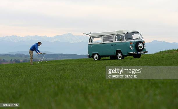 Volkswagen Kombi owner Wanja Fuhrmann sets up a camping table next to his Volkswagen T2 camper van built in the year 1975 near Landsberg southern...