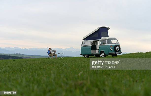 Volkswagen Kombi owner Wanja Fuhrmann sits on a camping chair and reads a newspaper next to his Volkswagen T2 camper van built in the year 1975 near...