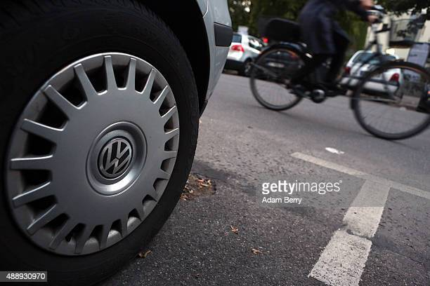 Volkswagen logo is seen on one of the automobile manufacturer's car's wheels as a bicycle passes on September 18 2015 in Berlin Germany The Obama...