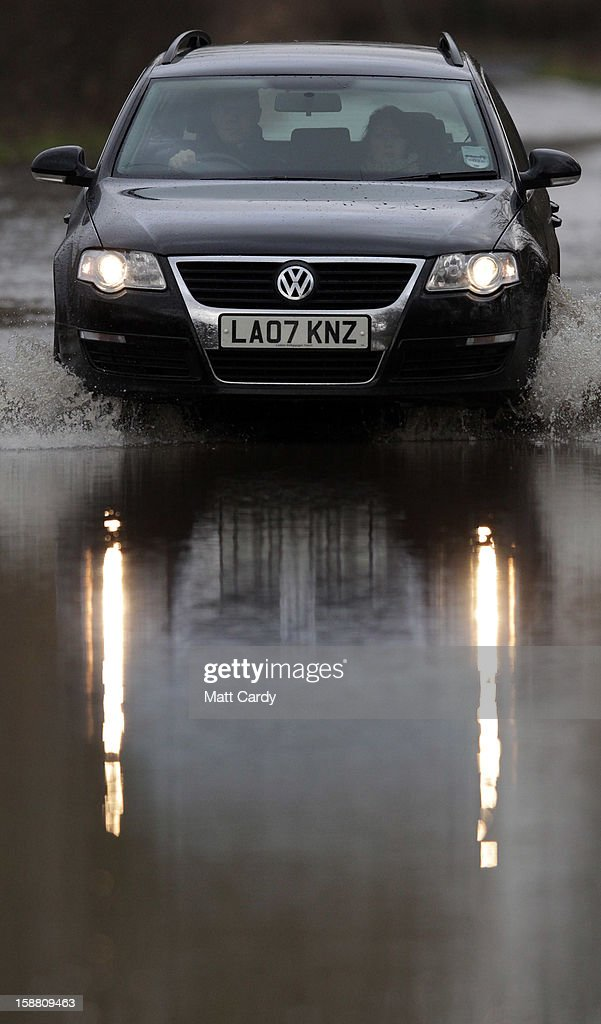 A Volkswagen Passat car drives through flood waters surrounding the village of Muchelney, which has been cut off by flooding on the Somerset Levels, on December 30, 2012 near Langport, England. The Met Office is warning of the risk of further flooding towards the end of the year, meaning 2012 is set to be the wettest on record.