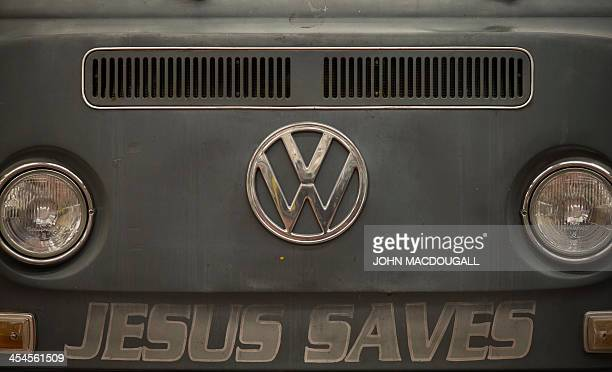A Volkswagen T2 van aka kombi or bulli with Jesus Saves painted on its front is on display at a Volkswagen workshop specialised in restoring vintage...