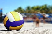 Volleyball ball on sandy beach with blur image of players playing in background