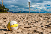 Volleyball in foreground with empty courts and nets on sandy beach beyond.