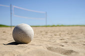 image of a volleyball sitting in the sand with net in background
