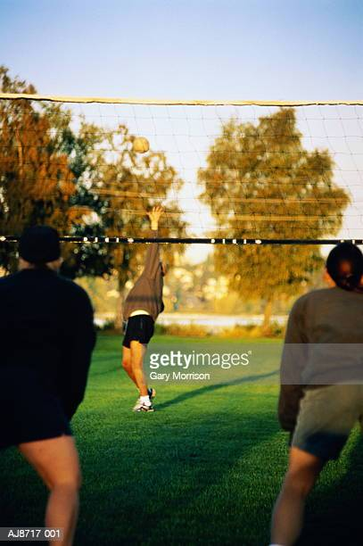 Volleyball player in park serving to waiting opponents
