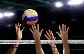 hand blocking volleyball spike over the net inside of a stadium