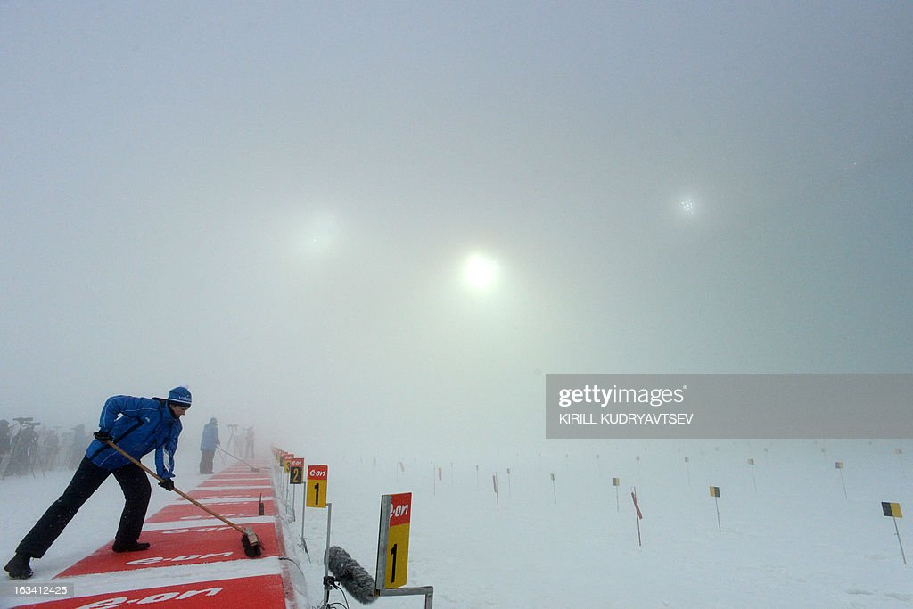 A volonteer prepares the shooting range in fog during a training session before Women 7.5 km Sprint during IBU World Cup Biathlon at Laura Cross Country and Biathlon Center in the Russian Black Sea resort of Sochi on March 9, 2013.