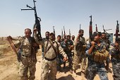 Volounteers who joined the Iraqi army to fight against Jihadist militants of the Islamic State brandish their weapons as they come as backup at a...
