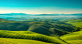 Volterra foggy panorama, rolling hills and green fields in the morning. Tuscany Italy, Europe