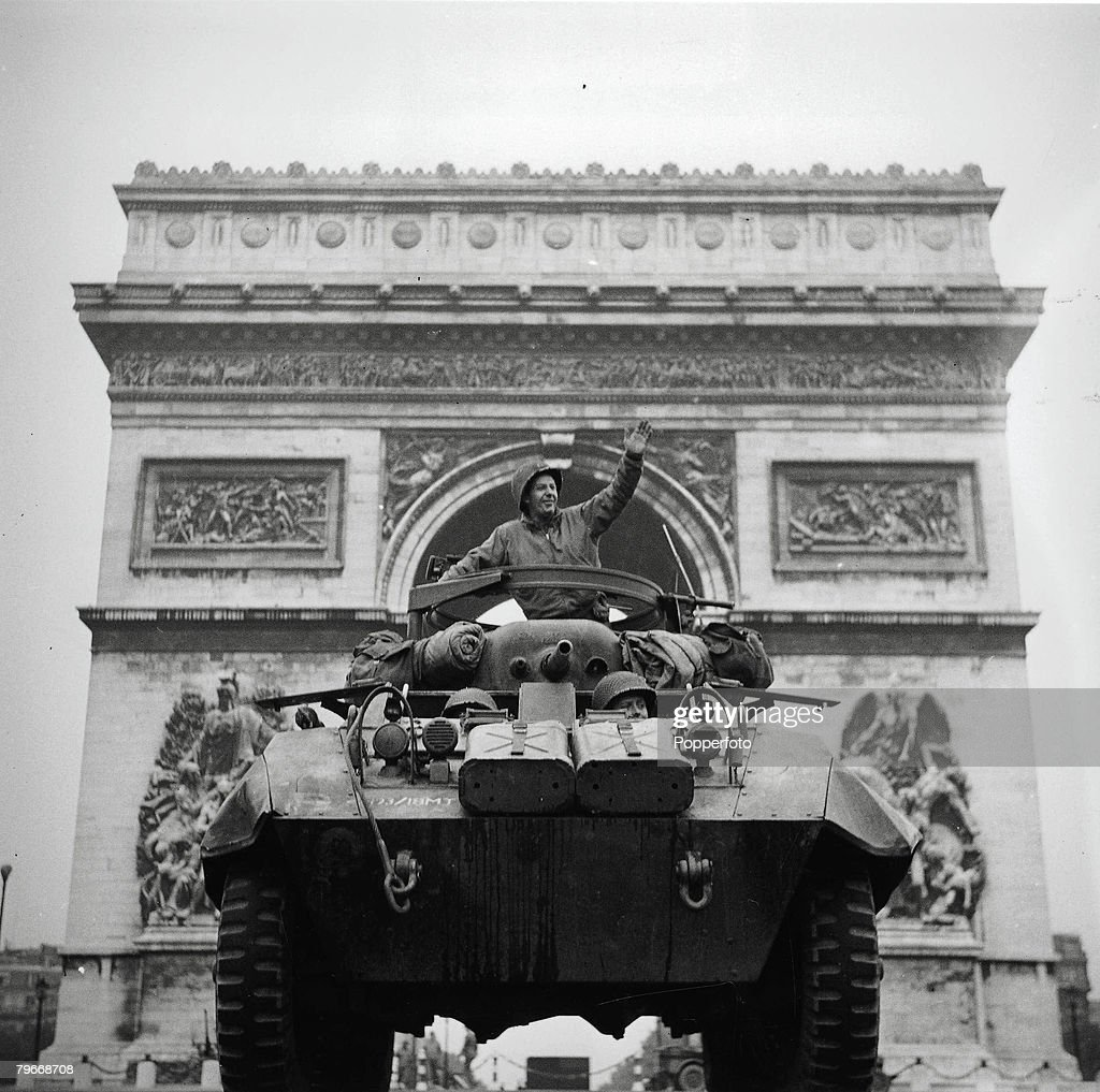 Volume 2, Page 128, Picture 2, World War Two, Paris, France, 31st August, 1944, Captain William Ruenzle of New Jersey waves from the turret of his armoured renaissance tank, situated in front of the Arc De Triomphe in Paris as the first American vehicle enters the city during the Allied invasion and liberation of Europe