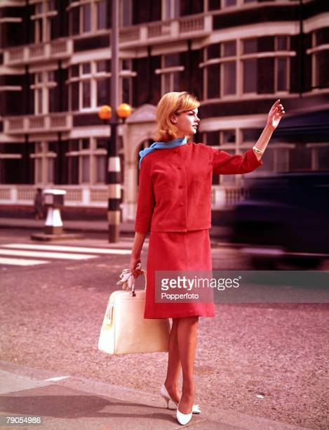 Volume 2 Page 52 Picture 5 London English model Jean Shrimpton hails a taxicab whilst wearing a red suede suit with cardigan jacket