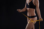 Volume legs with measuring tape. Woman after diet slimming weight loss on black background. Copy space