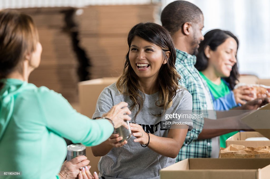 Volunteer accepts canned food donation at food drive : Stock Photo