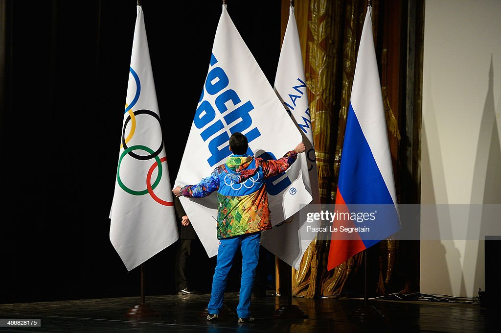 A Volunteer adjusts a flag on stage during the opening of the IOC session on February 4, 2014 in Sochi, Russia.