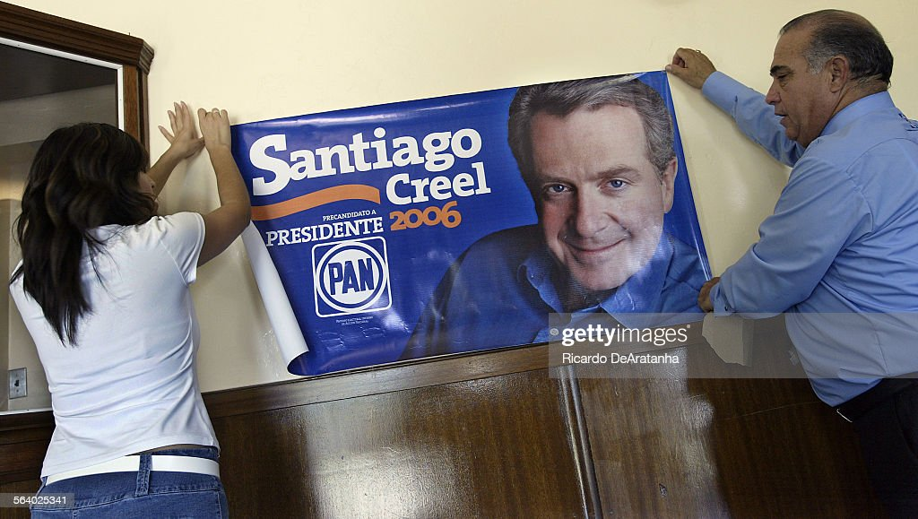 Volunteer Alison Mejia left and Representative Mario Martinez putting up a banner of Santiago Creel Mexican presidential candidate for PAN party This...