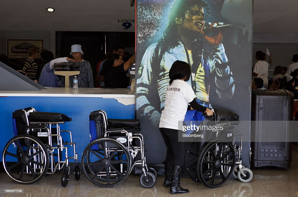 A volunteer arranges wheel chairs in front of a wall poster of Michael Jackson as patients receive medical attention during the Care Harbor Public Health Clinic event at the Los Angeles Sports Arena in Los Angeles, California, U.S., on Thursday, Oct. 31, 2013. The rate of uninsured Americans dropped slightly for the second consecutive year in 2012, a result of more people enrolling in Medicare and Medicaid, the U.S. Census Bureau reported Tuesday. Photographer: Patrick Fallon/Bloomberg via Getty Images