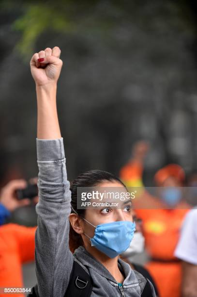 A volunteer asks for silence during the search for survivors in a flattened building in Mexico City on September 20 2017 after a strong quake hit...
