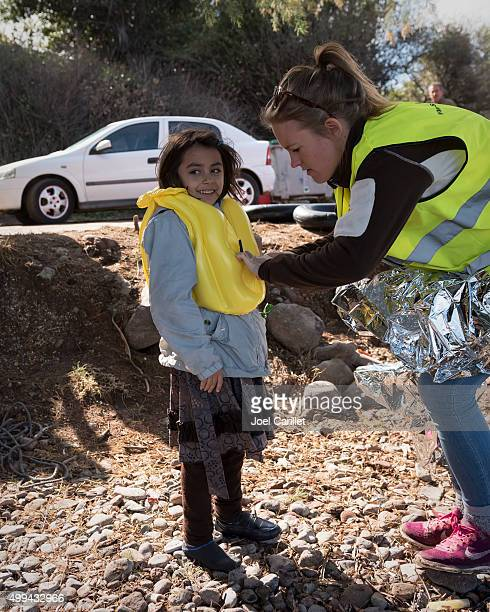 volunteer assisting refugee girl on Lesbos, Greece