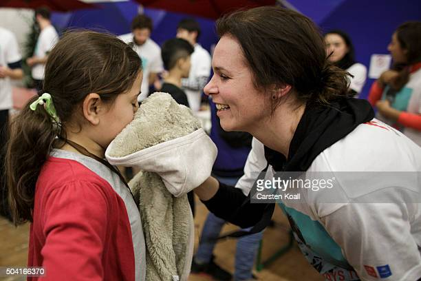 A volunteer at a shelter for migrants and refugees run by the Berliner Stadtmission charity plays with a girl with clothing donated by Japanese...