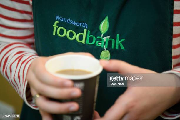A volunteer at Wandsworth foodbank drinks a cup of tea as others prepare the parcels for guests from their stores of donated food toiletries and...