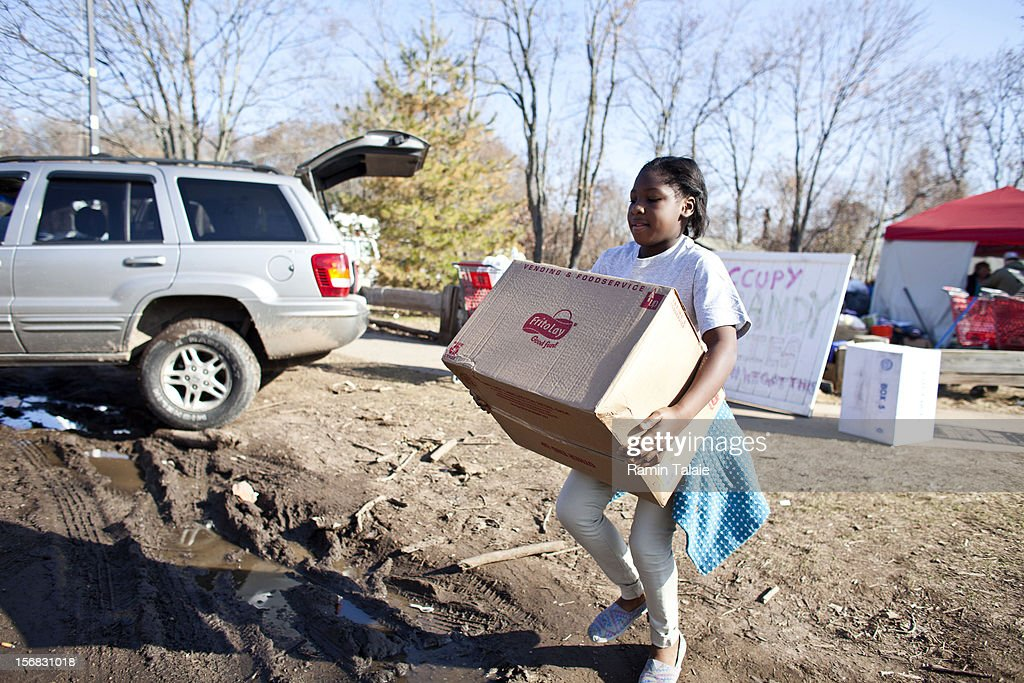 A volunteer carries a box of supplies at an Occupy Sandy distribution center to help victims of Superstorm Sandy on November 22, 2012 in the Staten Island borough of New York City. Sections of Staten Island were hard hit by flooding from Superstorm Sandy.