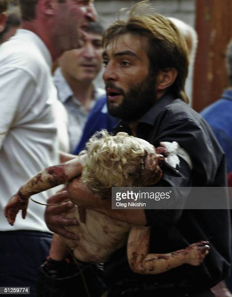 A volunteer carries an injured child after special forces stormed a school seized by Chechen separatists on September 3 2004 in the town of Beslan...
