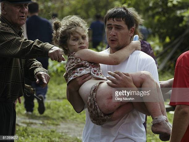 A volunteer carries an injured girl after special forces stormed a school seized by Chechen separatists on September 3 2004 in the town of Beslan...
