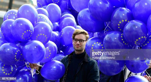 A volunteer carries balloons with the EU logo during the 'March For Europe' demonstration in Berlin on March 25 2017 to mark the 60th anniversary of...
