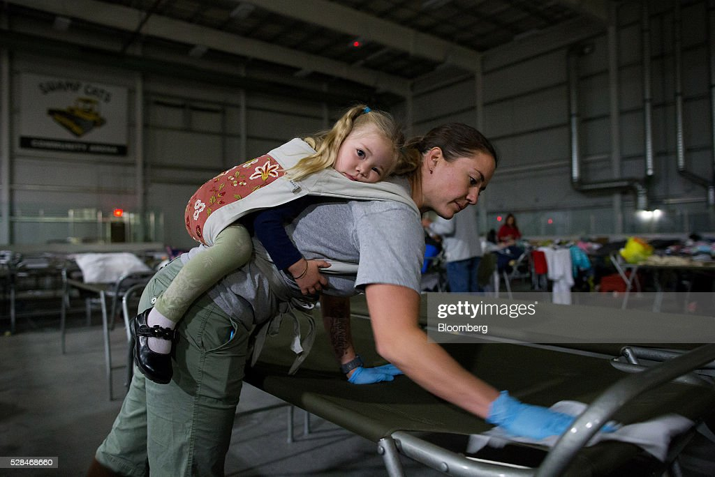 A volunteer carries her daughter while cleaning cots for Fort McMurray wildfire evacuees at a hockey rink in Lac La Biche, Alberta, Canada, on Thursday, May 5, 2016. A fire fueled by shifting winds that forced more than 80,000 people to flee their homes and threatened the business district of oil-sands hub Fort McMurray, Canada, raged out of control Wednesday after consuming 80 square kilometers (30 square miles) of land and damaging 1,600 buildings. Photographer: Darryl Dyck/Bloomberg via Getty Images