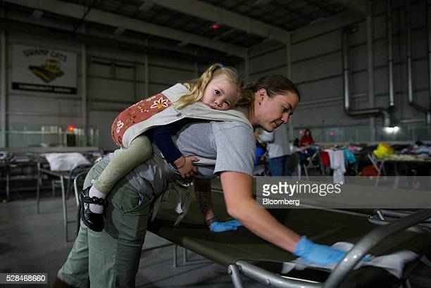 A volunteer carries her daughter while cleaning cots for Fort McMurray wildfire evacuees at a hockey rink in Lac La Biche Alberta Canada on Thursday...