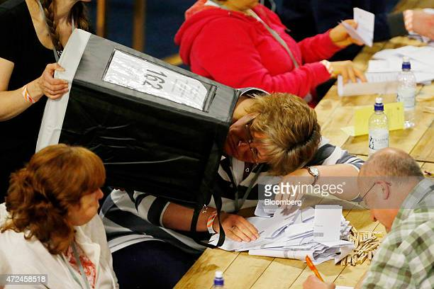 A volunteer checks to see that the ballot box is empty as votes are emptied onto the table for counting inside the English Institute of Sport...