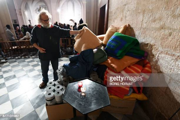 A volunteer collects covers as members of association and migrants occupy the church of Saint Ferreol in Marseille on November 21 to protest against...
