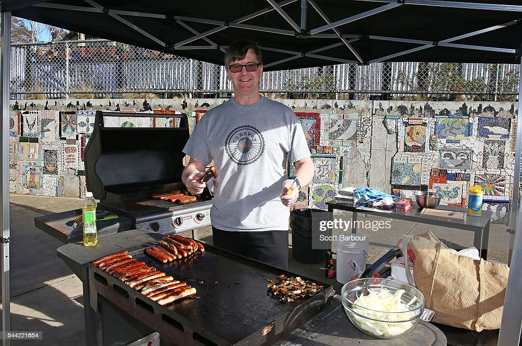 A volunteer cooks sausages at a sausage sizzle as people vote in the national election at a polling station on July 2, 2016 in Melbourne, Australia. Voters head to the polls today to elect the 45th parliament of Australia.