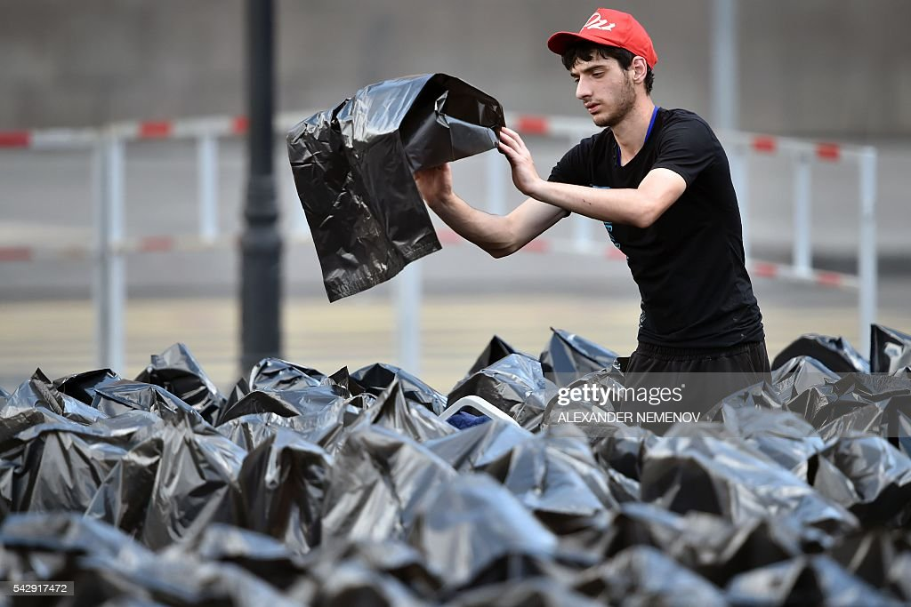 A volunteer covers VIP seats in plastic bags to protect them from the rain in Yerevan's Republic Square on June 25, 2016, where the pontiff is slated to hold a prayer for peace. / AFP / ALEXANDER