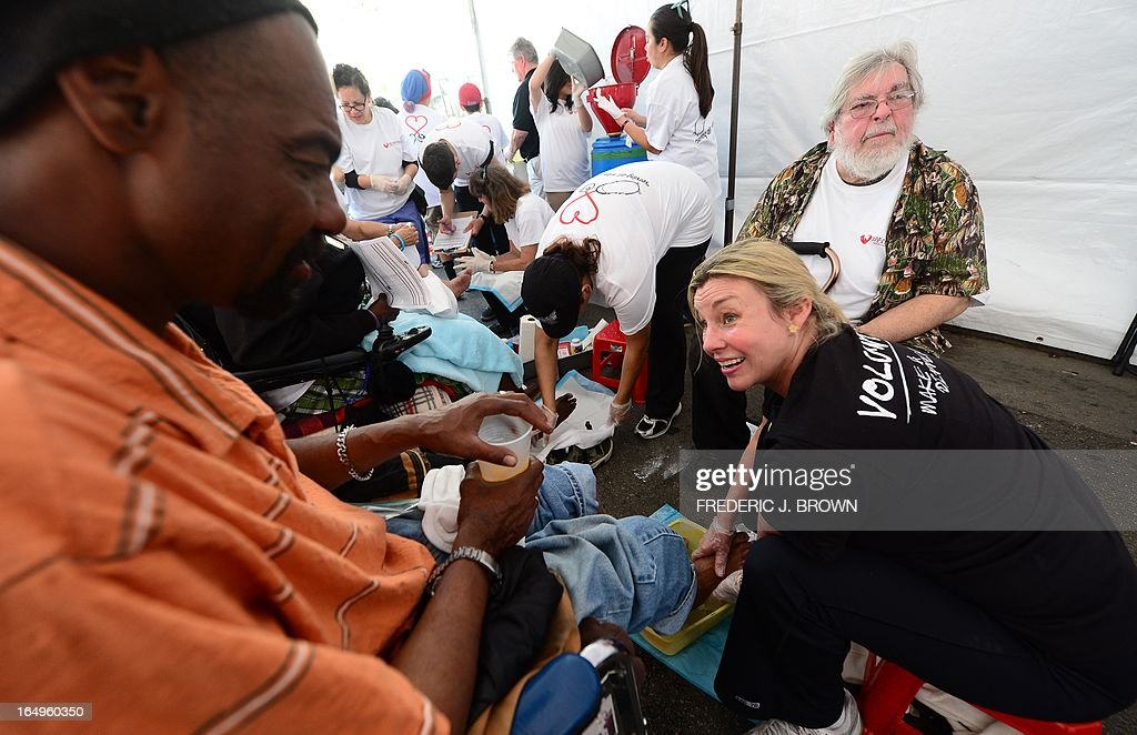 Volunteer Cyntia Joyce gives Skinnie (L) a foot wash as people gather at the Los Angeles Mission's Good Friday event on Skid Row on March 29, 2013 in Los Angeles, California. Celebrities and volunteers joined together in giving something back to this community of the homeless, among the largest in the US, who were fed a fully-prepared meal and had the opportunity to be given foot washing and hygiene kits. Foot washing, a symbolic ritual of humbleness and respect derived from Jesus Christ's washing of his disciples feet at the Last Supper, was offered by the Los Angeles Health Center and volunteers. AFP PHOTO/Frederic J. BROWN