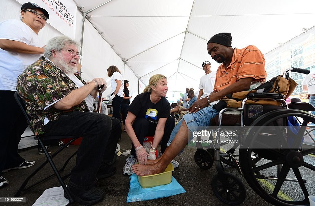 Volunteer Cyntia Joyce gives Skinnie, on a wheelchair, a foot wash as people gather at the Los Angeles Mission's Good Friday event on Skid Row on March 29, 2013 in Los Angeles, California. Celebrities and volunteers joined together in giving something back to this community of the homeless, among the largest in the US, who were fed a fully-prepared meal and had the opportunity to be given foot washing and hygiene kits. Foot washing, a symbolic ritual of humbleness and respect derived from Jesus Christ's washing of his disciples feet at the Last Supper, was offered by the Los Angeles Health Center and volunteers. AFP PHOTO/Frederic J. BROWN