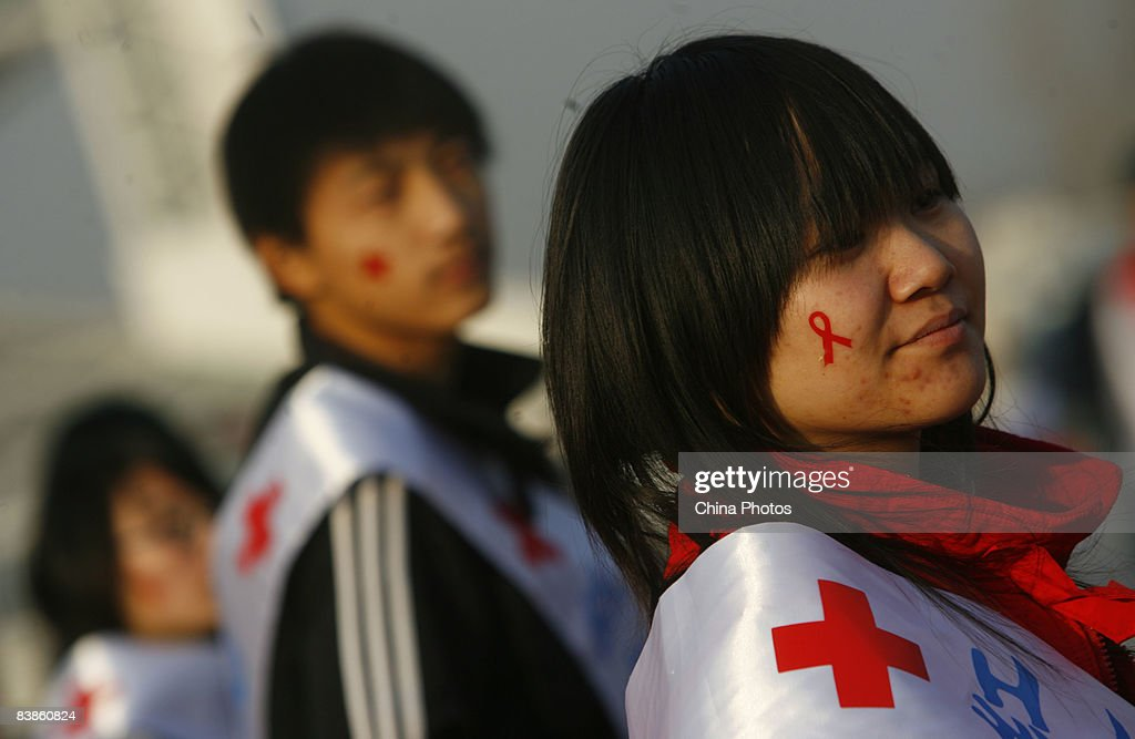 A volunteer decorates her face with a red ribbon during an AIDS awareness promotion at the National Stadium to mark the upcoming World AIDS Day on November 30, 2008 in Beijing, China. According to official estimates China has 700,000 people living with HIV with an estimated 85,000 with AIDS.