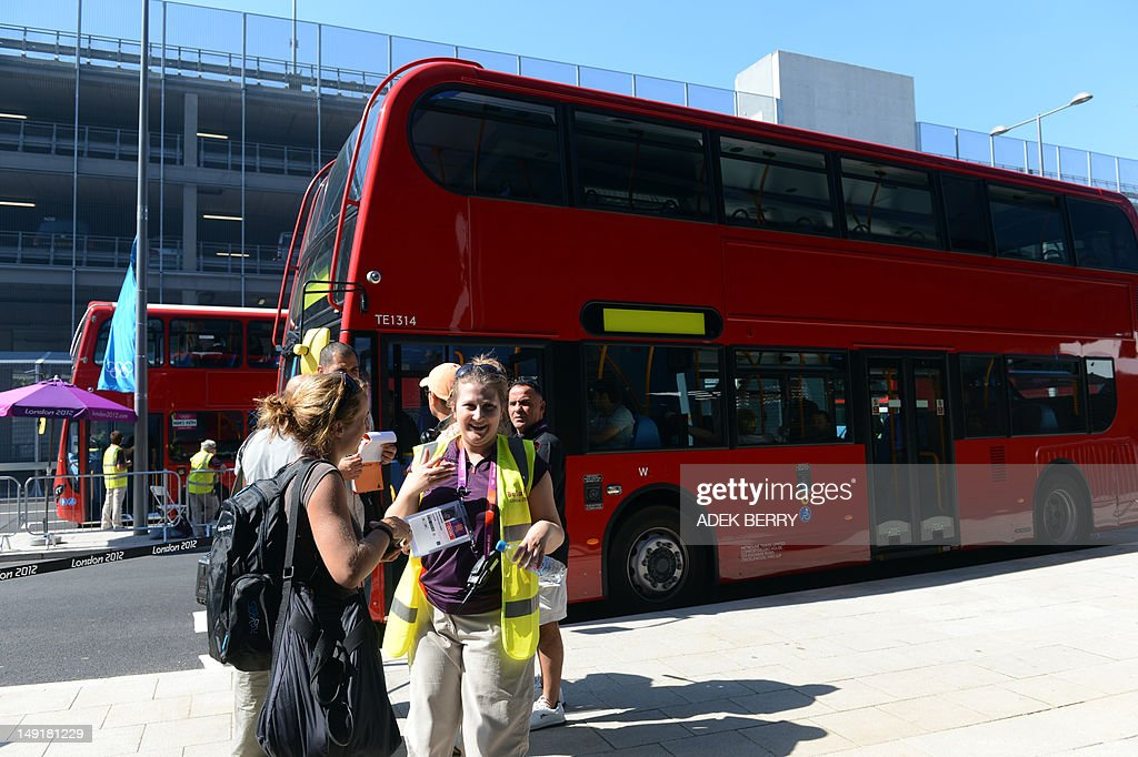 A volunteer directs journalists to their buses outside the Main Press Center in London on July 24 2012 three days before the start of the London 2012...