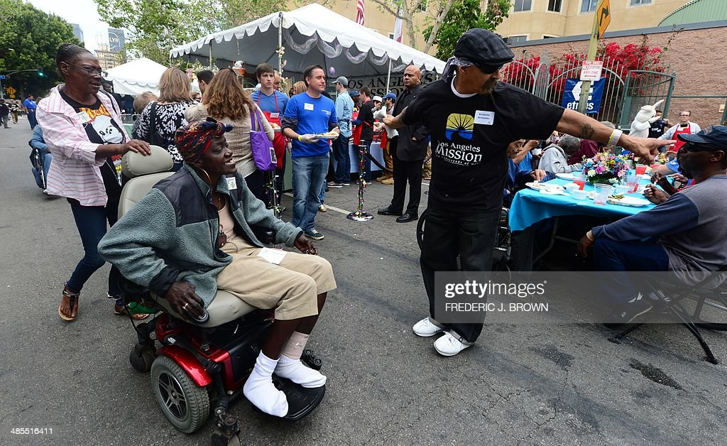 A volunteer directs the way to a seat at a table at the annual Good Friday meal hosted by the LA Mission and served by volunteers and celebrities for the homeless on Skid Row on April 18, 2014 in Los Angeles, California. For more than 75 years, the LA Mission has helped serve the needs of the down and out in downtown Los Angeles, providing emergency service like shelter, food , clothing as well as professional medical and dental services. AFP PHOTO/Frederic J. BROWN