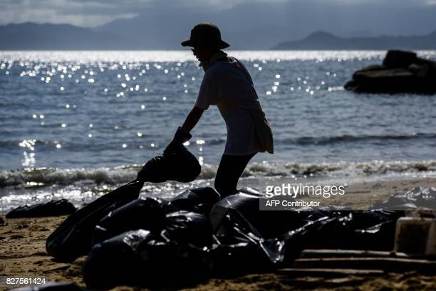 A volunteer drags a black bin bag as she helps remove washed up palm oil from a beach on Hong Kong's outlying Lamma Island on August 8 2017 Residents...