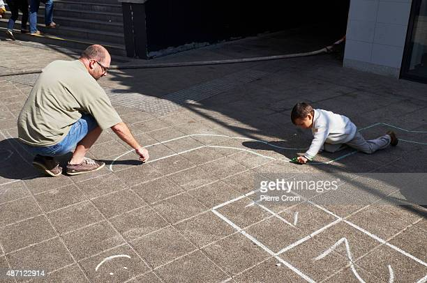 A volunteer draws a road on the floor of the Keleti train station as a Syrian child plays with a toy car on September 6 2015 in Budapest Hungary...