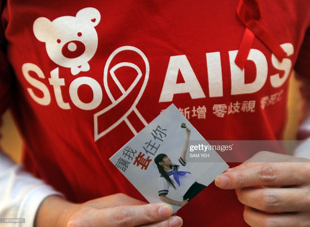 A volunteer dressed in red T-shirt holds a packet containing a condom to mark World AIDS Day at a train station in Taipei on December 1, 2012. Taiwan's health department organised the event to boost the awareness for HIV/AIDS prevention. AFP PHOTO / Sam Yeh / AFP / SAM YEH