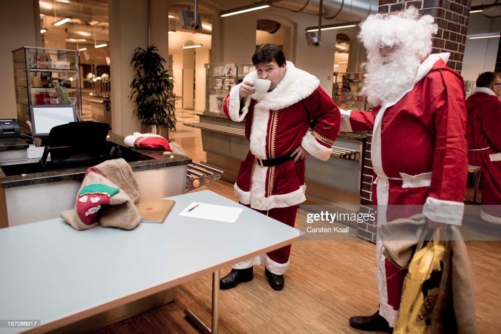 A volunteer drinks a cup off coffee as students dressed as Santas and angels gather for their annual, pre-Christmas gathering at the cafeteria of the Studentenwerk Nord student support service on December 1, 2012 in Berlin, Germany. The students, mostly from Berlin Technical University (Technische Universitaet Berlin), have completed a Santa workshop and will visit company parties in December and families on Christmas Eve as a way to make a little money to help fund their studies.