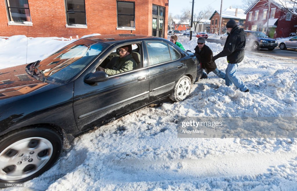 A volunteer driver and two other volunteers help push a woman's car stuck in the snow December 21, 2012 in Madison, Wisconsin. Wisconsin was blanketed with a snow storm Thursday.
