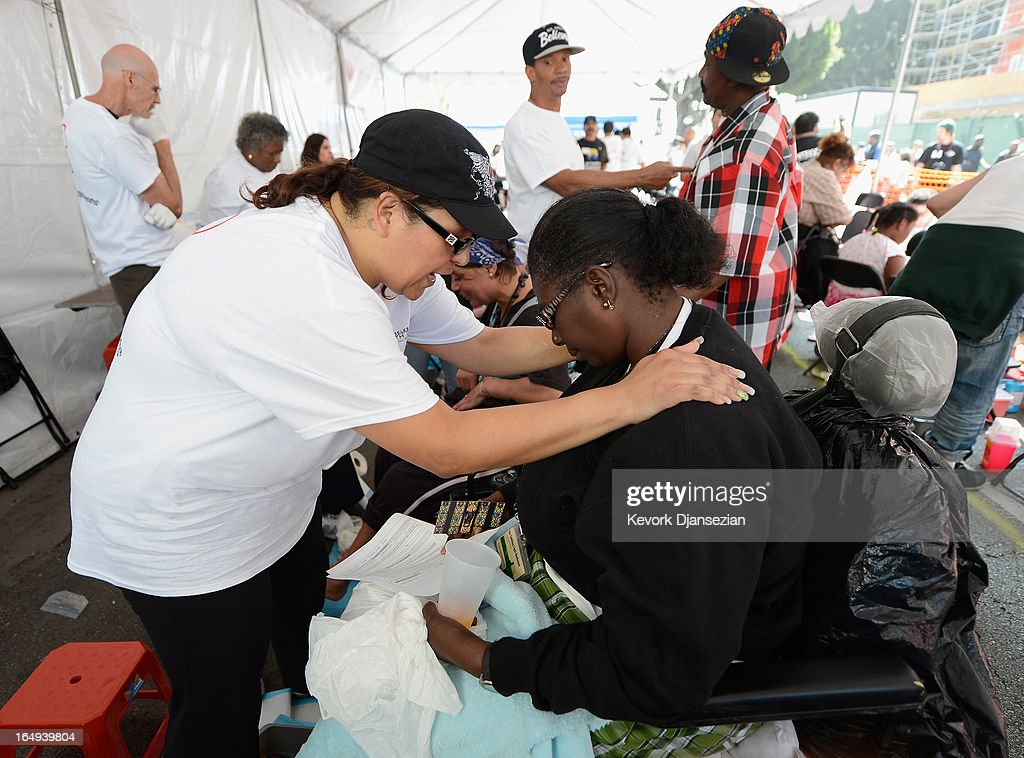 Volunteer Elsa Jones (L) prayes with Mary Woods after washing her feet during a Good Friday event at the Los Angeles Mission on Skid Row on March 29, 2013 in Los Angeles, California. Volunteers, celebrities and nurses provided 3,500 hot meals, 2,000 pairs of shoes, and more than 1,000 Easter baskets for children and podiatric care for the homeless of Skid Row.
