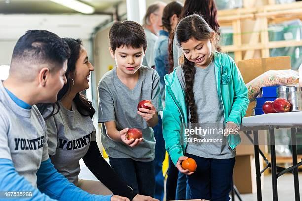 Enfants aider les parents trier les dons en effectuant du bénévolat ensemble