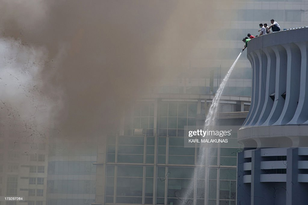 Volunteer firemen on top of a high-rise building spray water towards over a fire engulfing a shanty town in the financial district of Manila on July 11, 2013. There were no immediate reports of casualties from the blaze, which occurred mid-morning amid government plans to relocate thousands of families living in areas vulnerable to floods and typhoons.